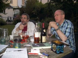 Owen Holland and Alan Winfield sharing memes and wine in the garden.